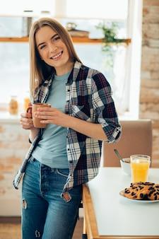 Glimlachende vrouw in vrijetijdskleding die bij de tafel staat en een mok vasthoudt