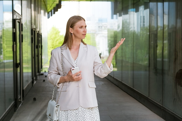 Glimlachende vrouw in vrijetijdskleding die bij de zakenvrouw op kantoor staat met een mobiele telefoon in haar hand...
