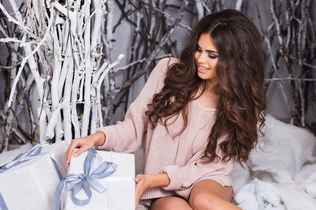 Glimlachende vrouw in warme, gezellige kleding met witte geschenkdoos op winter