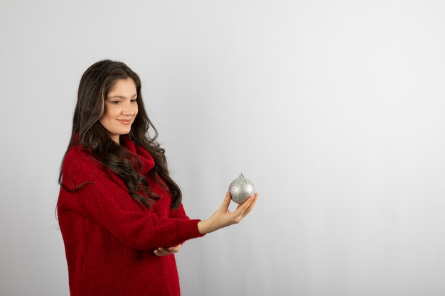 Glimlachende vrouw in warme rode trui die een kerstbal aanbiedt.