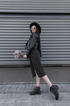 Glimlachende vrouw in zonnebril in modieuze hoed in stijlvolle zwarte kleding met boeket van lila poses in de buurt van grijze muur in de stad. aantrekkelijke trendy gelukkig meisje met schattige glimlach geniet van prachtige bloemen.