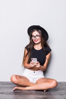 Glimlachende vrouw in zwarte hoedenzitting op de vloer en het gebruiken van smartphone die over grijze achtergrond wordt geïsoleerd