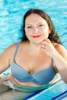 Glimlachende vrouw in zwembroek bij het hotelzwembad. verticale foto