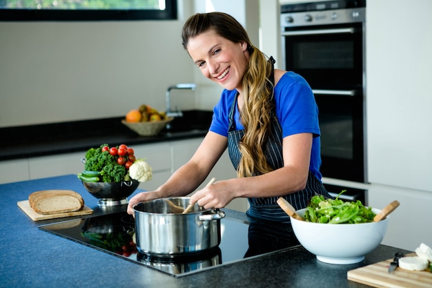 Glimlachende vrouw koken groenten in een pan op een fornuis
