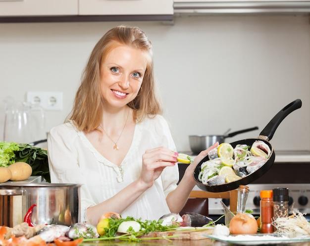 Glimlachende vrouw koken vis met citroen
