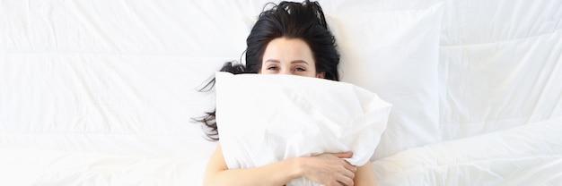 Glimlachende vrouw ligt op wit bed en knuffelt kussen, gezonde slaap en vecht tegen slapeloosheid