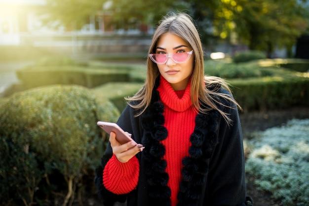 Glimlachende vrouw loopt door de straat in het centrale park en gebruikt haar telefoon