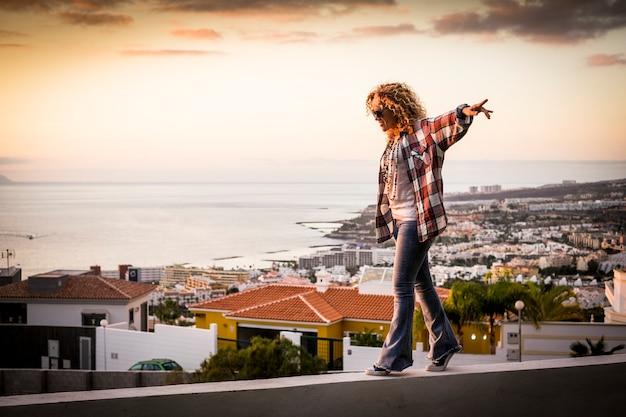 Glimlachende vrouw loopt evenwichtig over een prachtige stadskustlijn