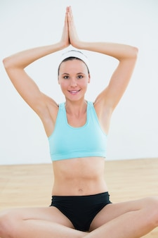 Glimlachende vrouw met aangesloten bij handen lucht bij geschiktheidsstudio