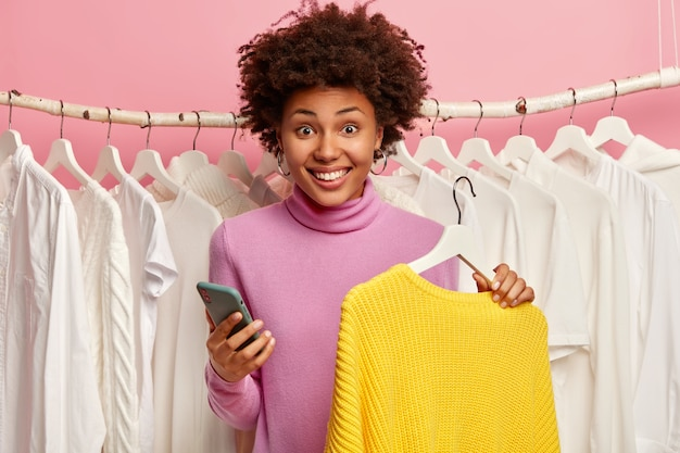 Glimlachende vrouw met afro-haar, gebruikt gsm-app om online te betalen, koopt nieuwe gele trui, staat achter kledingstang