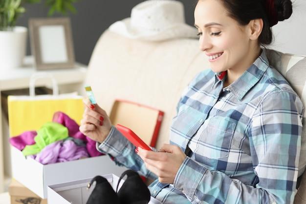 Glimlachende vrouw met bankkaart en smartphone zittend op de bank met een doos schoenen online