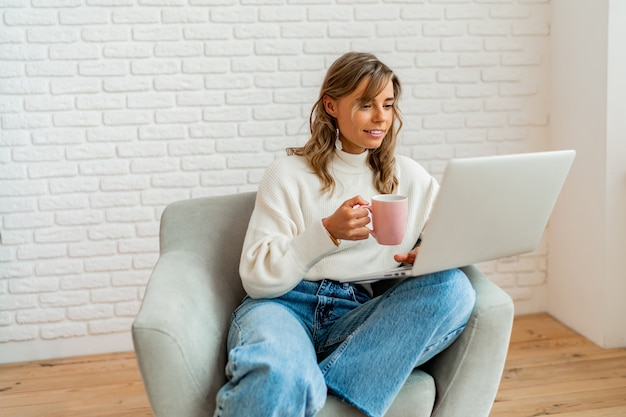 Glimlachende vrouw met blonde golvende haren die thuis op de bank zit te werken op een laptopcomputer en een kopje koffie vasthoudt