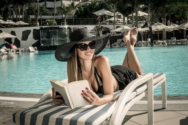 Glimlachende vrouw met boek op poolside