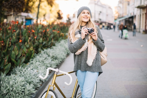 Glimlachende vrouw met camera en fiets