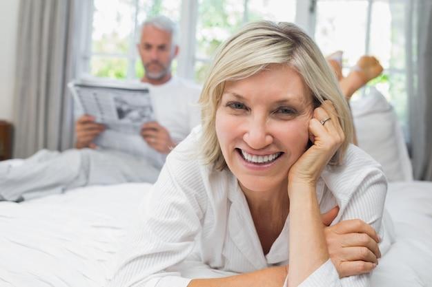 Glimlachende vrouw met de krant van de mensenlezing in bed
