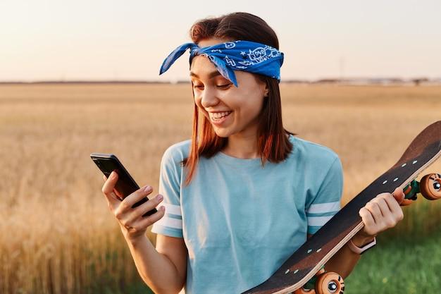 Glimlachende vrouw met donker haar met t-shit en haarband in handen skateboard en smartphone, kijkend naar het display van de mobiele telefoon met geluk, uitstekend nieuws uit het bericht lezend.