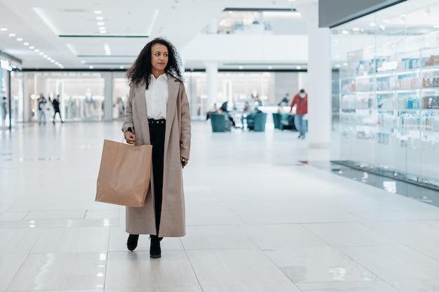 Glimlachende vrouw met een boodschappentas wandelen in de gang van een supermarkt