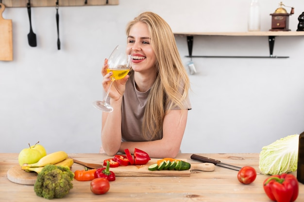Glimlachende vrouw met een glas en groenten bij de keuken