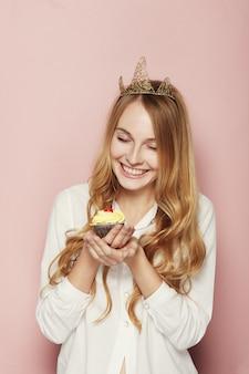 Glimlachende vrouw, met een kroon, die een verjaardag houdt cupcake