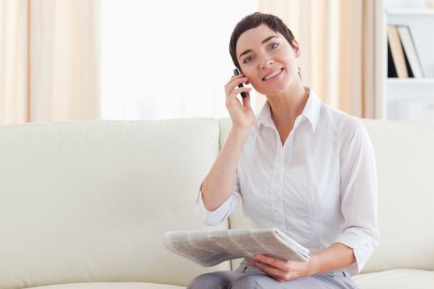 Glimlachende vrouw met een mobiel en een krant
