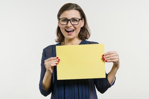 Glimlachende vrouw met geel vel papier