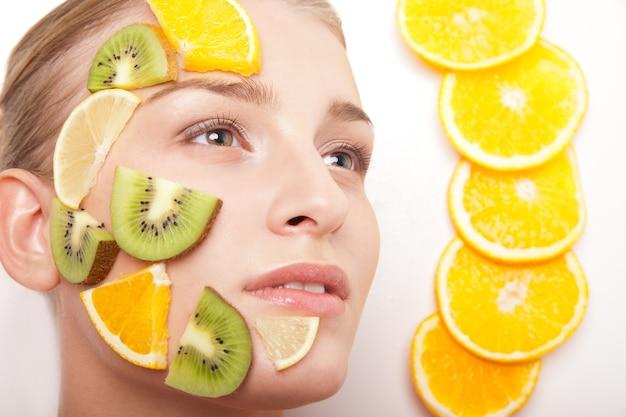Glimlachende vrouw met geïsoleerd fruitmasker op haar gezicht