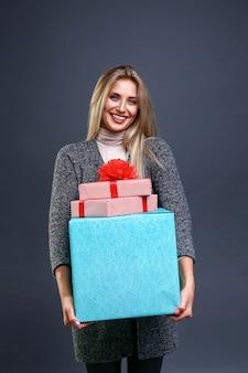 Glimlachende vrouw met geschenkdozen