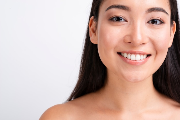 Glimlachende vrouw met gezond huid dicht omhoog portret