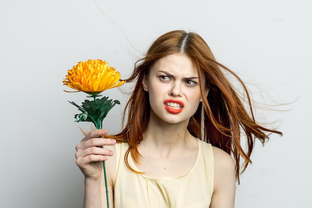 Glimlachende vrouw met grote gele bloem in de vreugde van handenemoties