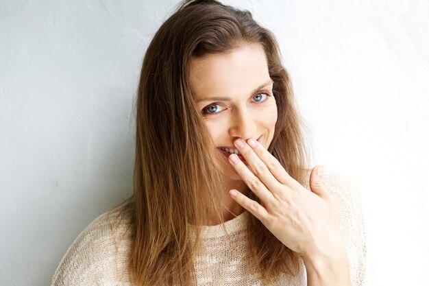 Glimlachende vrouw met hand die mond behandelt