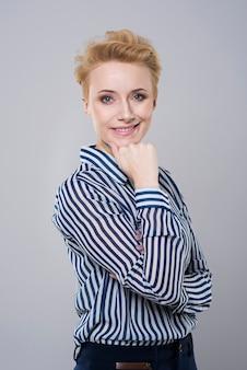Glimlachende vrouw met hand op haar kin