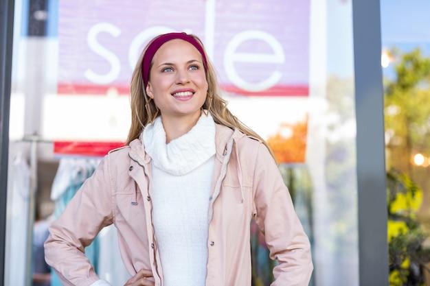 Glimlachende vrouw met handen op heupen voor verkoopteken