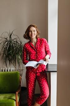 Glimlachende vrouw met het tijdschrift van de kort haarholding. binnen schot van lachende jonge vrouw in rode pyjama in de woonkamer.