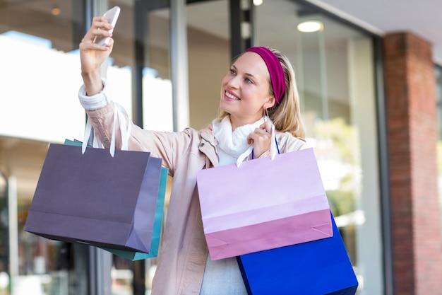 Glimlachende vrouw met het winkelen zakken die selfies nemen