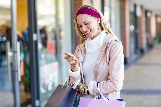 Glimlachende vrouw met het winkelen zakken die smartphone gebruiken