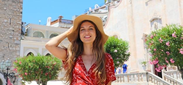 Glimlachende vrouw met hoed in taormina-dorp op het eiland van sicilië, italië