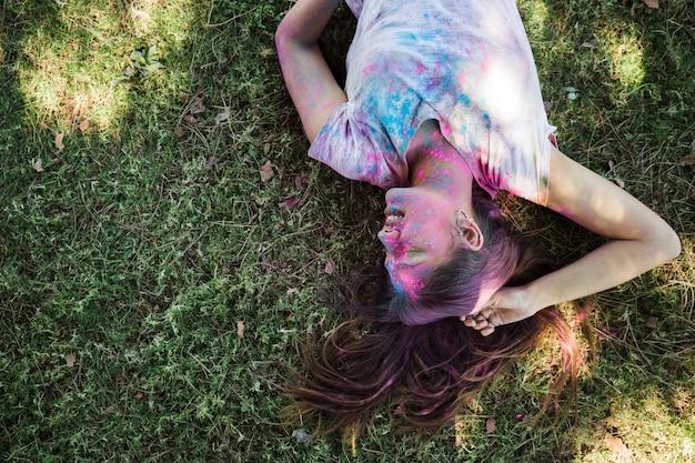 Glimlachende vrouw met holikleuren die op groen gras liggen