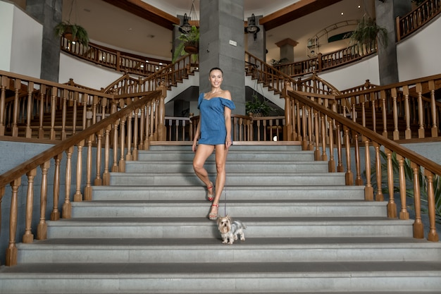 Glimlachende vrouw met hond het stellen op stappen