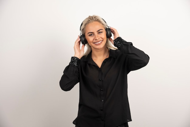 Glimlachende vrouw met hoofdtelefoons die zich op witte achtergrond bevinden. hoge kwaliteit foto
