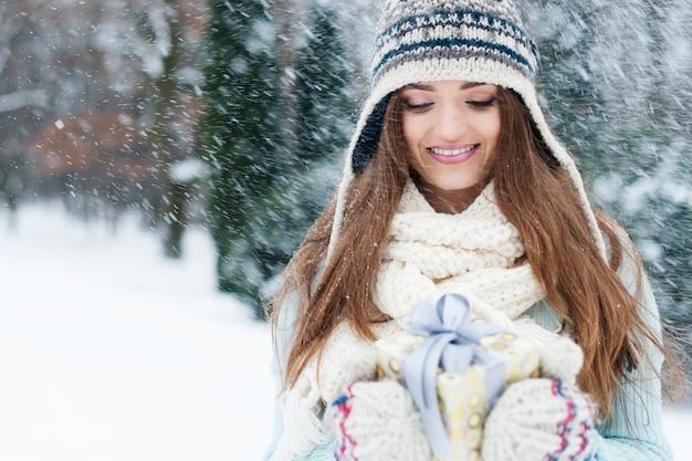 Glimlachende vrouw met klein cadeautje tijdens het sneeuwen