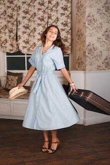 Glimlachende vrouw met koffer en witte hoed in haar handen.