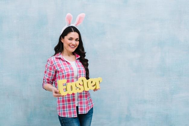 Glimlachende vrouw met konijntjesoor die pasen-woord tonen tegen blauwe geweven achtergrond