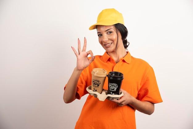 Glimlachende vrouw met koppen die ok gebaar tonen