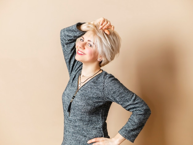 Glimlachende vrouw met korte stoel, haar hand op kop