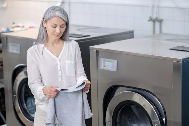Glimlachende vrouw met lang grijs haar die zich dichtbij wasmachines bevinden die gewassen t-shirt in chemisch reinigen bekijken