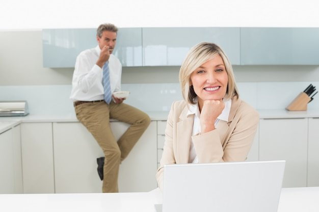 Glimlachende vrouw met laptop en man op achtergrond bij keuken