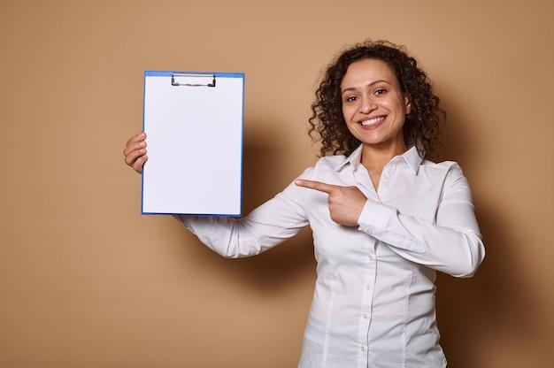 Glimlachende vrouw met mooie brede glimlach die haar wijsvinger op wit leeg document blad op klembord richt, die zich tegen beige muur met exemplaarruimte bevindt