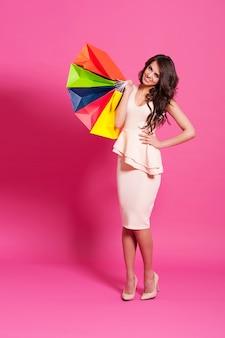 Glimlachende vrouw met multi gekleurde boodschappentassen