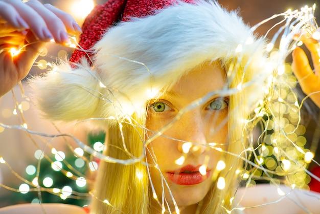 Glimlachende vrouw met rode lippen. kerstlicht. meisje draagt kerstmuts. concept van vakantie. kerststemming. winter vakantie. sexy.