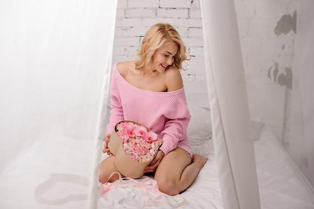 Glimlachende vrouw met roze overhemdszitting op het bed die de doos met bloemen openen die aan de kant kijken